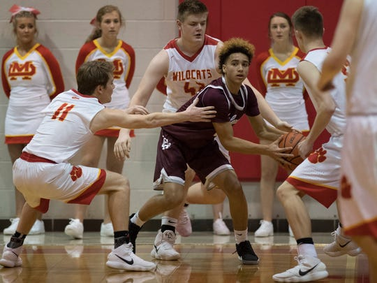 Henderson County's Kale Gaither is surrounded by Mater Dei players during the Bosse Winter Classic Saturday afternoon.