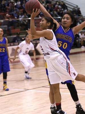 Shiprock's Chamika Begaye drives past Bloomfield's Alyssa Quintana for a layup attempt on Friday at the Chieftain Pit in Shiprock.