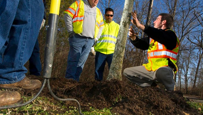 Knoxville's Urban Forester Kasey Krouse, right, teaches proper mulch application to city workers including Gary Lundy, left, and Jimmy Underwood in 2013 at Victor Ashe Park.