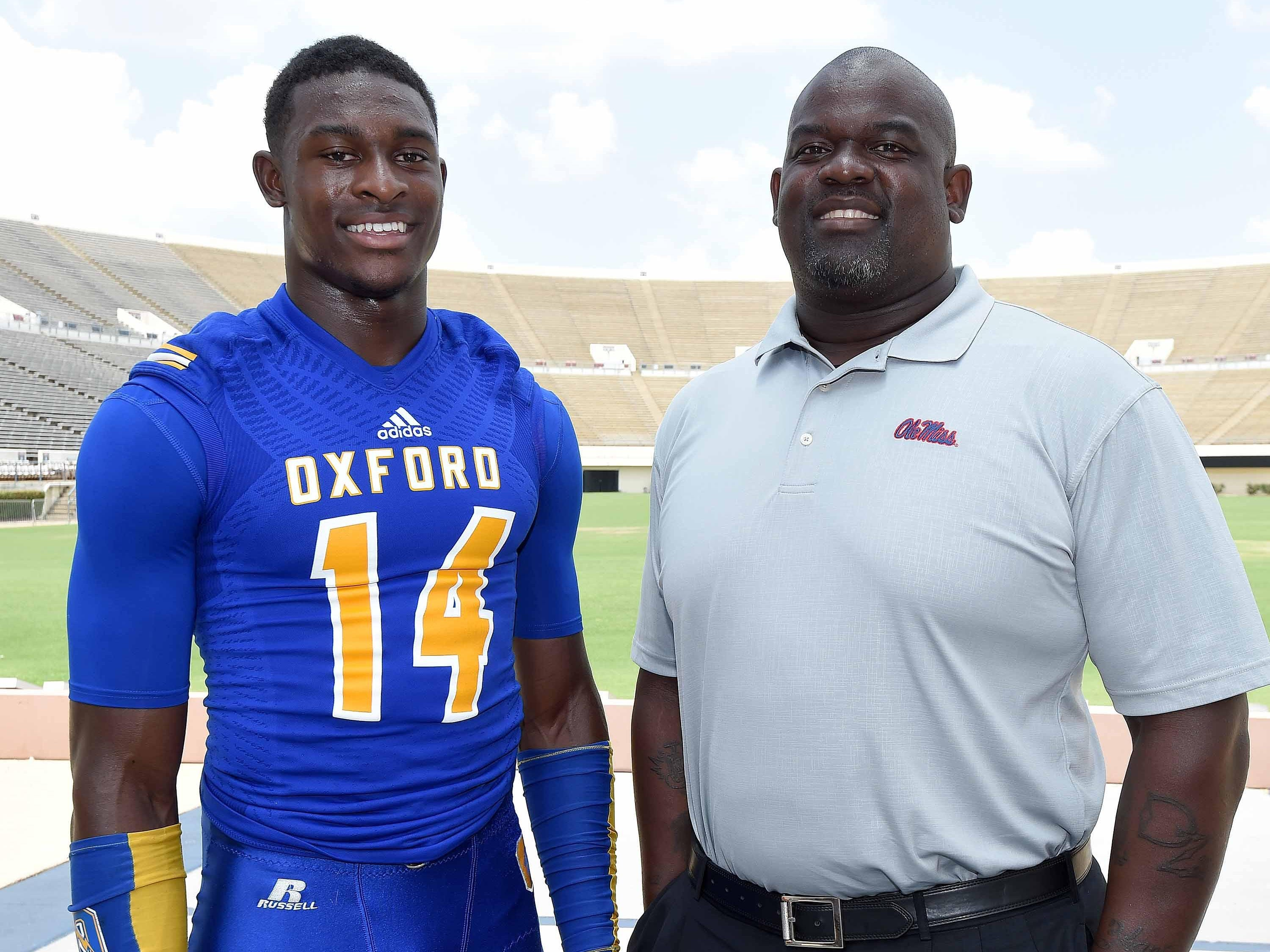 Oxford senior wide receiver D.K. Metcalf and his father Terrence Metcalf pose for pictures at the Dandy Dozen photo shoot at Mississippi Veterans Memorial Stadium on July 28. D.K. is following in his father's footsteps, having committed to play for Ole Miss. The two get to share the field together as Terrence is the team's defensive line coach.