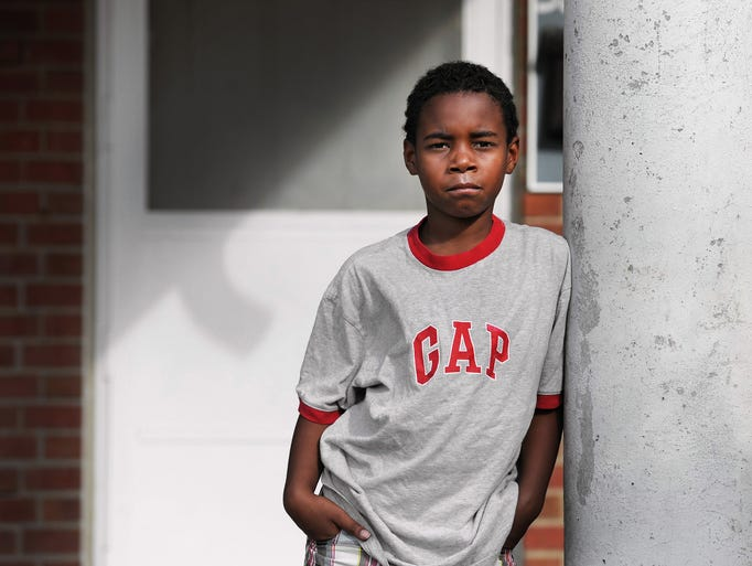 Damarcus Cole, 9 of Indianapolis, stands outside the building where he lives at the Hawthorne Place Apartments off 32nd and Emerson on Thursday, September 13, 2013. Mom Tyeisha Tillman is looking to move out of the complex to provide a better environment for her five children as three people have been killed on the grounds since May.