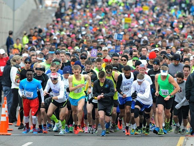 Runners leave the starting line on University Drive during Saturday's Earth Day Half Marathon in St. Cloud.