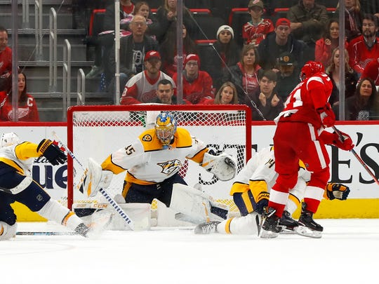 Detroit Red Wings center Dylan Larkin (71) scores  against Nashville Predators goaltender Pekka Rinne (35) during overtime in an NHL hockey game Friday, Jan. 4, 2019, in Detroit. (AP Photo/Paul Sancya)