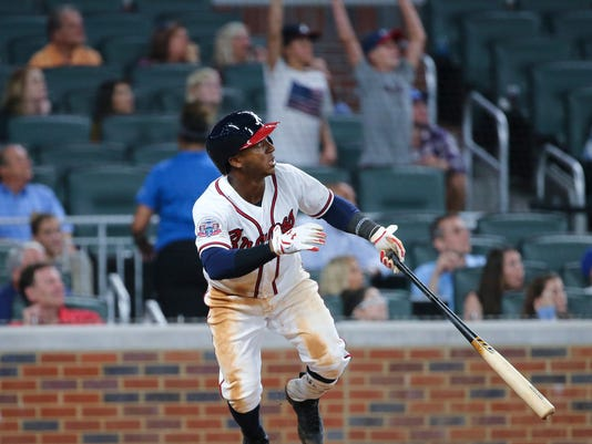 Atlanta Braves' Ozzie Albies watches his three-run home run during the ninth inning of the team's baseball game against the Los Angeles Dodgers on Thursday, Aug. 3, 2017, in Atlanta. The Dodgers won 7-4. The homer was Albies' first career hit. (AP Photo/John Bazemore)