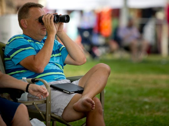 Ken Cazabon, of Washington Township, watches boats run time trials with binoculars during the 2015 St. Clair Riverfest.