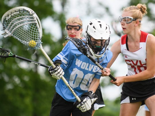 CVU's Bella Rieley (10) guards South Burlington goalie Claire Phillips (00) during the girls lacrosse game between the South Burlington Wolves and the Champlain Valley Union Redhawks at CVU High School on Wednesday afternoon June 6, 2018 in Hinesburg.