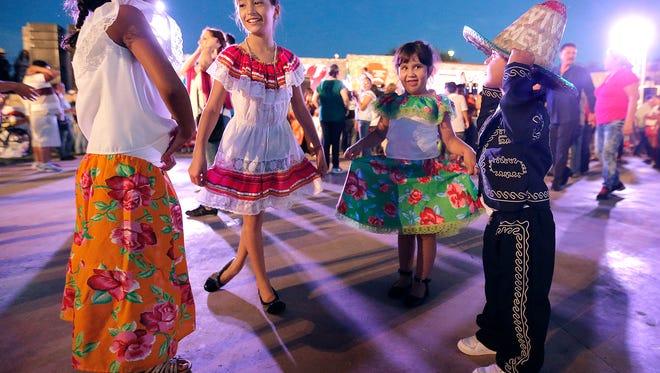 Los niños bailan con música tradicional mexicana mientras esperan a El Grito durante la celebración del 16 de septiembre en el Monumento Nacional Chamizal.  El Grito de Dolores se originó en el pequeño pueblo de Dolores cerca de Guanajuato el 16 de septiembre de 1810, comenzando la Guerra de Independencia de México.