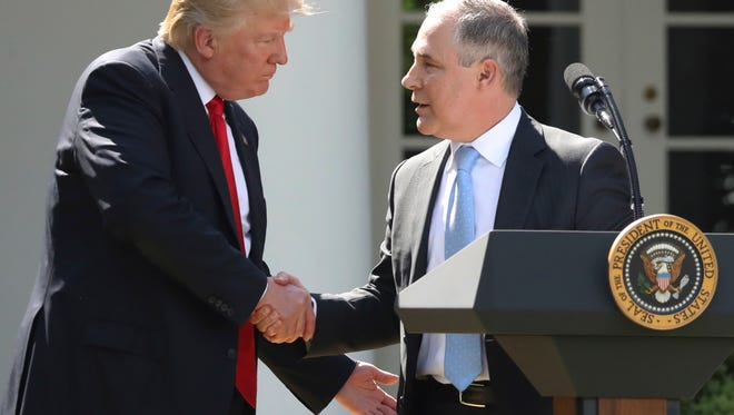 In this June 1, 2017 file photo, President Donald Trump shakes hands with EPA Administrator Scott Pruitt in the Rose Garden of the White House in Washington.
