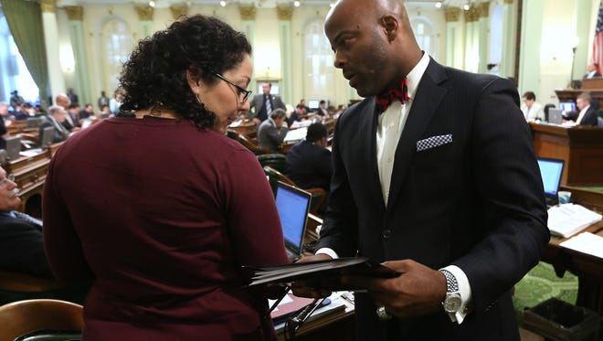 Calif. Assemblyman Isadore Hall, right, D-Compton, talks with Assemblywoman Cristina Garcia, D-Bell Gardens, during the Assembly session at the Capitol in Sacramento, Calif., Tuesday, May 27, 2014.