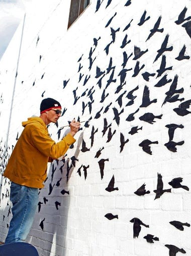 """Artist Brian Boner works on """"The Garden"""" mural on the west side of the MonOrchid Building on Roosevelt Street in Phoenix. The mural is part of efforts to raise awareness for the homeless."""