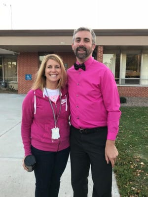 Kellie Ruedinger, third-grade teacher at Emmeline Cook Elementary School and Dr Eric Smiltneek take part Oct. 20 in a special community walk to school with many students and staff joining in to raise awareness about breast cancer.