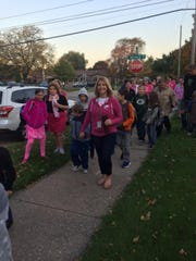 Kellie Ruedinger, third-grade teacher at Emmeline Cook Elementary School, leads a special community walk to school Oct. 20 with many students and staff joining in to raise awareness about breast cancer.