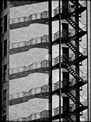 A fire escape and its shadows are seen from a parking lot of the Columbus Building (50 Chestnut St.).