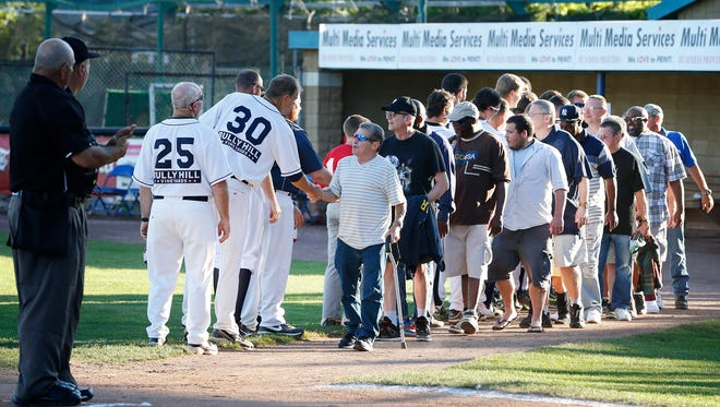 Veterans shake the hands of the Elmira Pioneers ball players Thursday before the first pitch. Veterans and the National Guard were celebrated during the inaugural New York Army National Guard Recognition Day at the local baseball field.