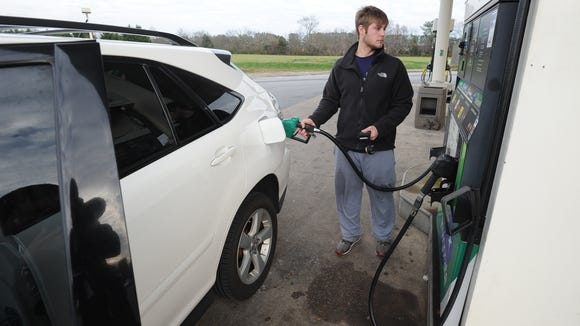 Tyler Williams of Felton pumps fuel at Uncle Willie's gas station on South DuPont Highway in Woodside on Dec. 18. A state lawmaker is proposing a 10-cent fuel tax.
