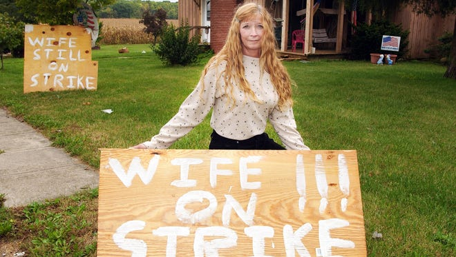 Kathy Thompson poses with her strike sign outside her home in Albany Ind.  Friday Sept. 27 2002. Thompson has gone out on strike for one week to get some help around the house from family members. Thompson works goes to school cooks cleans and when her husband left on a fishing trip with buddies it was the last straw. She and her husband are not fighting she just wants to gain some respect and help for all working  women and the extra work involved in keeping a home. (AP Photo/The Star Press Kyle Evens)