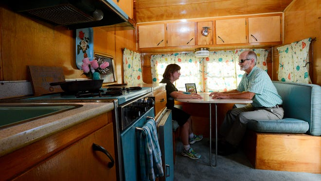 """Steve Viele and his daughter Liz sit at the table of their 1965 Frolic camper, nicknamed a """"canned ham"""" camper, Monday, Sept. 12, 2016 in Dimondale."""