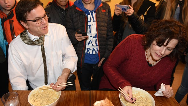 Meads Mill Middle School Principal Brad O'Neill mildly taunts his opponent, sixth-grade teacher Wendy Martin, on March 2 as the two begin a macaroni-and-cheese eating contest. The competition, held at Northville Township's Noodles and Co., was to benefit the school's Positive Behavior Intervention program. Students behind the two were alternately cheering and taking photos.