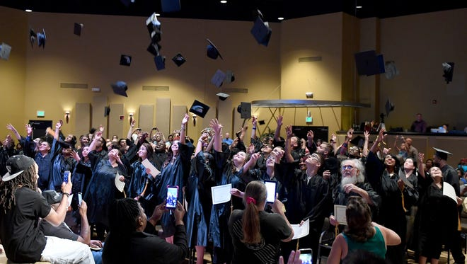 Family and friends take photos as graduates of the West Tennessee Adult Education District Seven throw their caps in the air after their graduation, Thursday, June 29, 2017.
