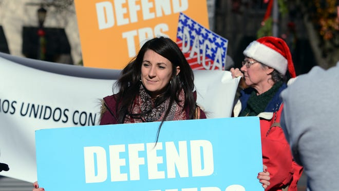 CASA lead organizer Laila Martin of Harrisburg displays a sign during an Indivisible YORK rally at Continental Square protesting immigration laws Friday, Dec. 1, 2017. Bill Kalina photo