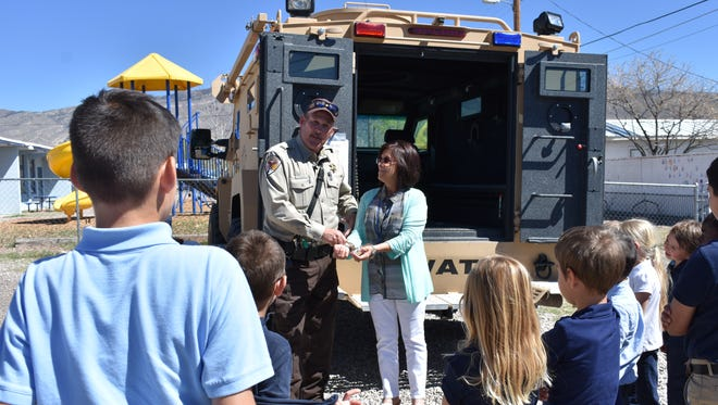 Otero County Sheriff's Office deputy Patrick O'Brien handcuffs Mercie Epperson, a fourth and fifth grade teacher at Father James B. Hay School, as part of a demonstration for students on Tuesday afternoon. The presentation was a thank you gift to the students for participating in the Blue Mass.