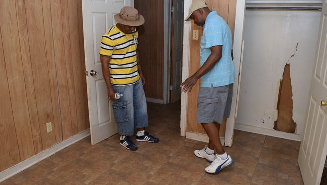 Luther Smith (right) shows Michael Smith how the foundation of the rental house Luther owns has shifted due to flooding that occurred twice in the past two years.