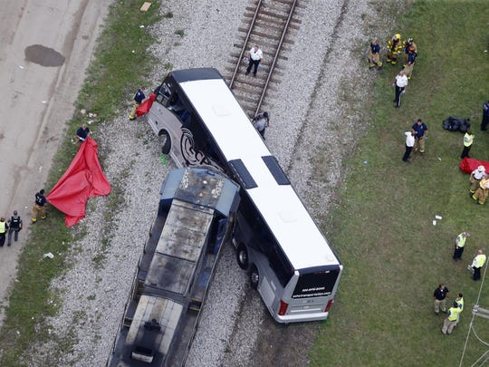 Responders works the scene where a train hit a bus in Biloxi, Miss., Tuesday, March 7, 2017. A freight train smashed into a charter bus in Biloxi, Mississippi, on Tuesday, pushing the bus 300 feet down the tracks authorities said. Authorities worked for more than an hour to remove passengers, Biloxi Fire Chief Joe Boney said, taking the injured people to area hospitals and cutting through the bus's mangled body to extract the final two people.