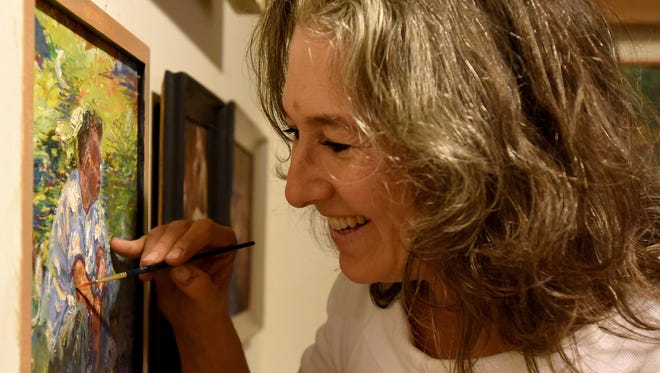 Painter Nora Daniel works on an acrylic painting in her home studio. Daniel paints a variety of subjects including landscapes, still lifes and portraits.
