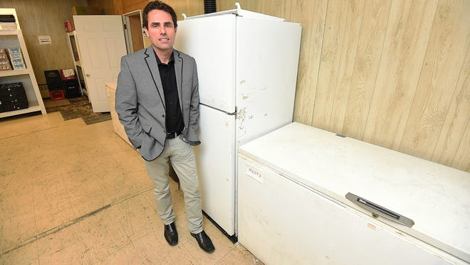 Jeff Quick, executive director of the Food Bank of North Central Arkansas, stands next to a freezer at the charity where someone stole approximately $250 worth of meat recently. Quick says there's no need to steal food from the charity as it distributes food freely to those in need.