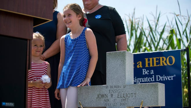 Nora Adamchak, 5, left, and her sister Anna Adamchak, 7, stand by their uncle's memorial during a dedication ceremony Friday, July 21, 2017 in Monroeville.