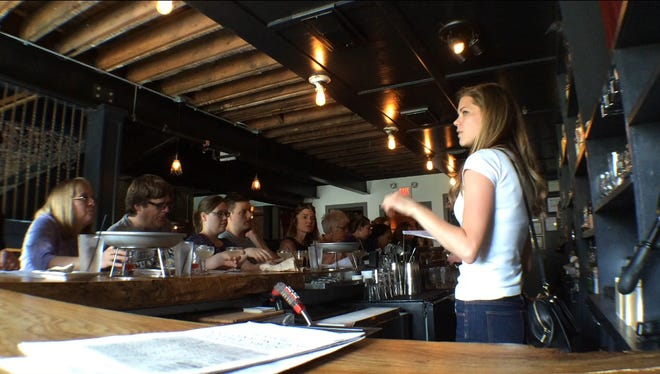 Rachel Wobeter, right, talks about the history of oyster bars and Iowa City's Goosetown Neighborhood as visitors sample oysters in half shells and cocktails from the Clinton Street Social Club during the Iowa's Culinary Heritage walking tour Sunday.