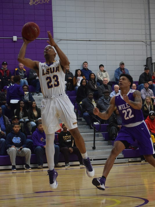 LSUA's Jordin Williams (23, left) scores two against Wiley College's Patrick Banks (22, right).