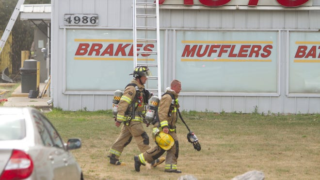 Brighton Area firefighters, accompanied by Green Oak Township firefighters, work a structure fire at an Auto Value store in the 4900 block of Old U.S. 23 Wednesday, July 11, 2018.