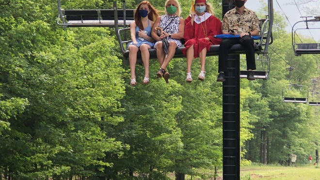 Canandaigua Academy graduate Alexi Farnes, with her family, rides to the summit of Bristol Mountain for her diploma on Sunday.