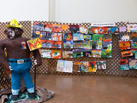 Children's paintings line a lattice wall behind a papier mache Smokey Bear at a New Mexico State Forestry exhibit during the home and garden show. The artwork came from primary grades all the way to high school.