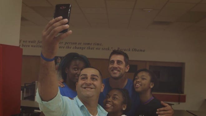 Aaron Rodgers poses for a group selfie at Milwaukee College Prep with Tony Gonzalez and three former students.