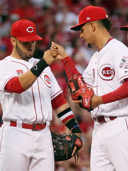 Cincinnati Reds' starting pitcher Luis Castillo gets congratulations from Eugenio Suarez, left, as he leaves in the sixth inning of a baseball game against the Milwaukee Brewers, Wednesday, June 28 2017, in Cincinnati. (AP Photo/Tony Tribble)