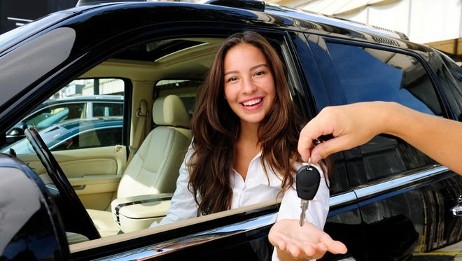 businesswoman receiving keys of her new off-road car from dealer
