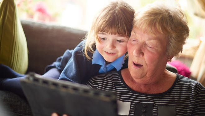 A grandmother and granddaughter are hugging looking at a digital tablet.