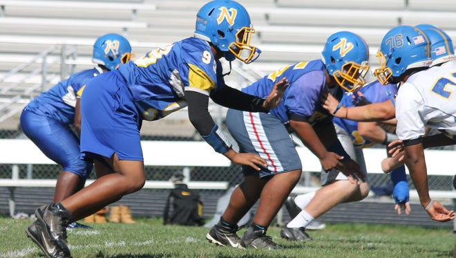 Northwest defensive lineman Michael Carter breaks from his stance as the ball is snapped during practice.