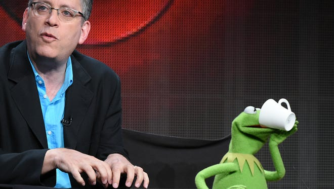 "Kermit the Frog takes a sip from his mug at ""The Muppets"" panel at the Disney/ABC Summer TCA Tour at the Beverly Hilton Hotel on Tuesday, Aug. 4, 2015, in Beverly Hills, Calif. Speaking at left is writer/executive producer Bill Prady."