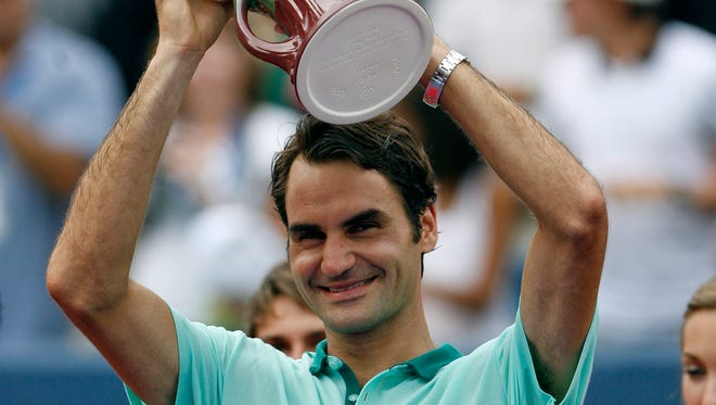 Roger Federer celebrates during the trophy presentation after defeating David Ferrer on day seven of the Western & Southern Open tennis tournament at Linder Family Tennis Center.