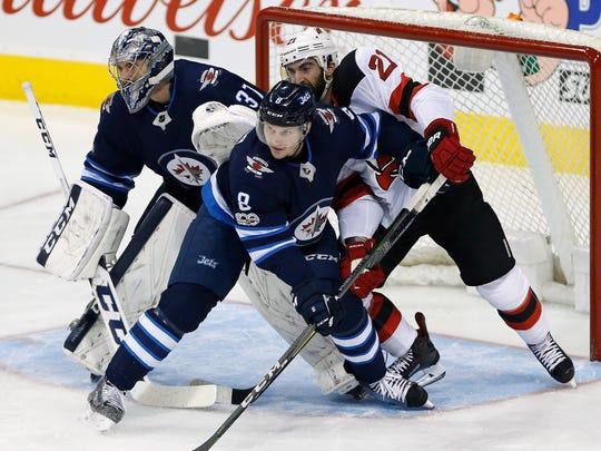 Winnipeg Jets' Jacob Trouba (8) and New Jersey Devils'