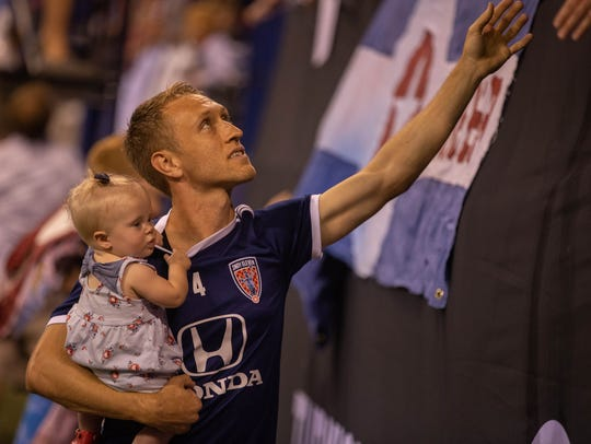 Brad Ring, holding his daughter, greets fans in the