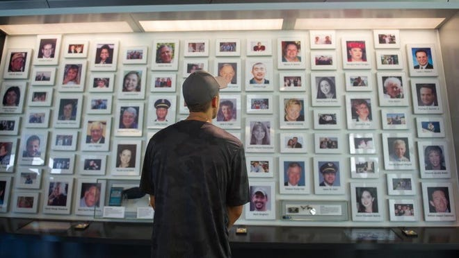A visitor looks through the portraits of Sept. 11 victims at the Flight 93 National Memorial in Shanksville, Pa. Nearby, the Sacred Ground plaza marks the point of the jet's impact in 2001.