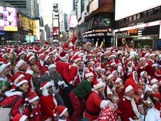 People dressed as Santa Claus and Mrs. Claus celebrate in Times Square as they gather for the annual Santacon festivities.
