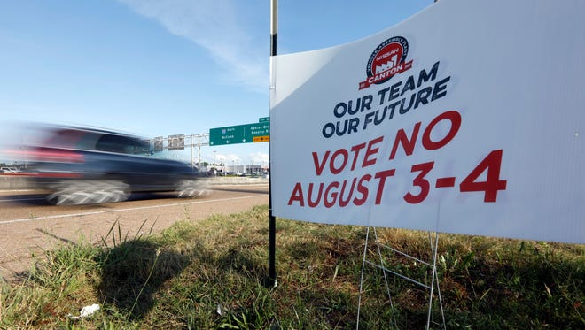 A vehicle drives past one of the anti-union signs that dot neighborhoods in Jackson, Miss.