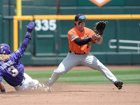 Omaha, NE, USA; Oregon State Beavers infielder Cadyn Grenier (2) makes a putout ahead of the slide from LSU Tigers infielder Kramer Robertson (3) in the first inning at TD Ameritrade Park Omaha.