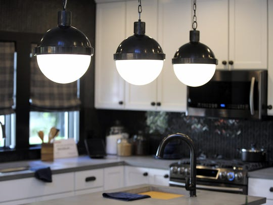 Three pendant lights hang over an island-prep sink in the kitchen.