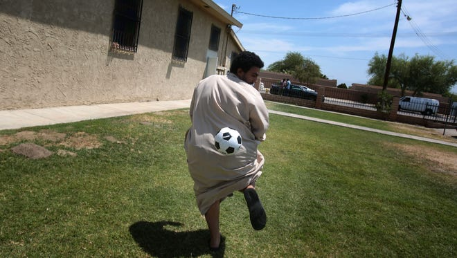 Ismael Alwishah, 20, of Indio plays with a soccer ball after the noon service at the Islamic Society of of Palm Springs on Friday, June 10, 2016 in Coachella.